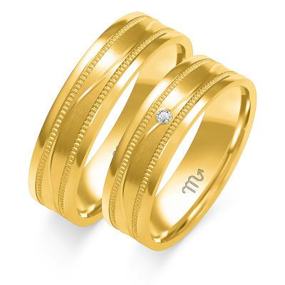 Złote obrączki ślubne z ozdobnymi brzegami i gustowną falą